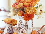 a woven tray with citrus and orange blooms in printed vases is a lovely idea for vintage Thanksgiving styling