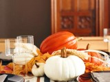 an all-natural Thanksgiving centerpiece of orange and white pumpkins, wheat, leaves are all you need to make your table cozy