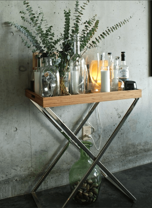 a home bar and decoration on a stand, lots of vintage bottles with a eucalyptus arrangement, some candles, a lamp and some alcohol