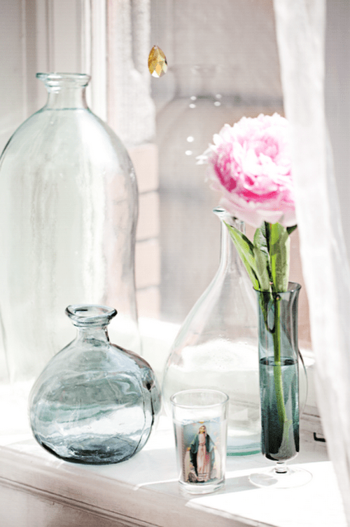 neutral and blue glass vases with flowers and just bottles placed on a windowsill add chic and interest to the space