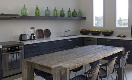 a moody kitchen with an open shelf and a row of green bottles that add color and highlight the vintage feel in the space