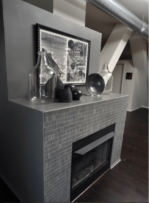 oversized neutral bottles and dark ceramics on the mantel make it look catchy, chic and interesting