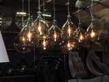 an arrangement of pendant lamps made of bottles hanging down is cool for any space