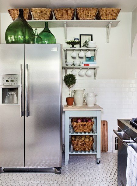 oversized green bottles on the fridge make the space look cooler and bolder and add a vintage feel to the kitchen