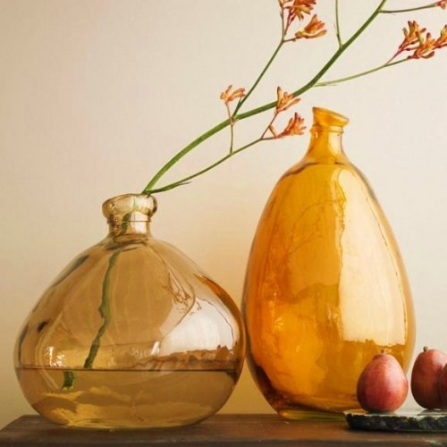 beautiful amber irregular bottles with some blooming branches are a refined decoration for a modern space