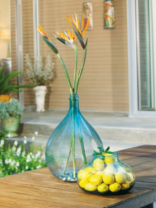 beautiful blue bottles with blooms and with lemons for decorating your spaces, indoor and outdoor ones