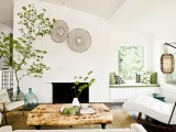oversized green bottles with green branches by the fireplace refresh the space and make it cooler and bolder