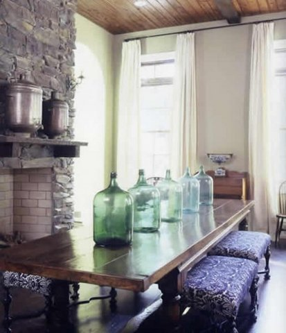 a farmhouse space with large green glass bottles that line up the table and add a vintage feel to the space