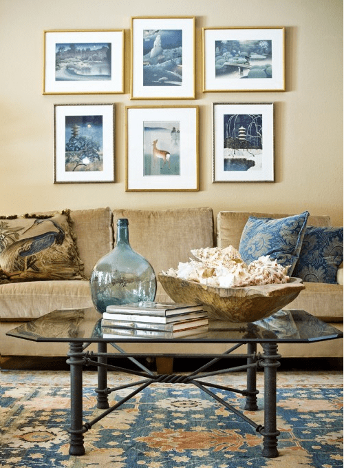 a seaside living room with an inspiring gallery wall, a bowl with seashells and a blue glass bottle on the table