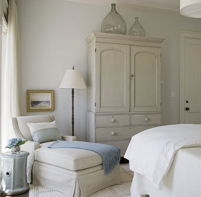 a neutral vintage bedroom with large bottles on the wardrobe that make it catchy and interesting